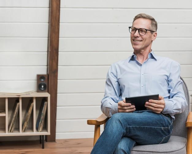 Uomo maturo di smiley che si siede e che tiene il suo ridurre in pani Foto Gratuite