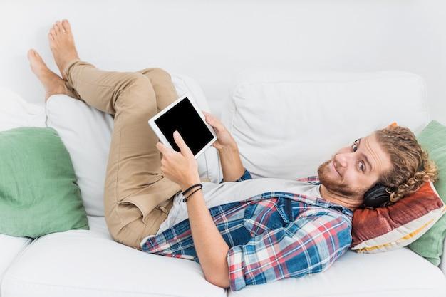 Uomo moderno che utilizza la tabella sul divano Foto Gratuite