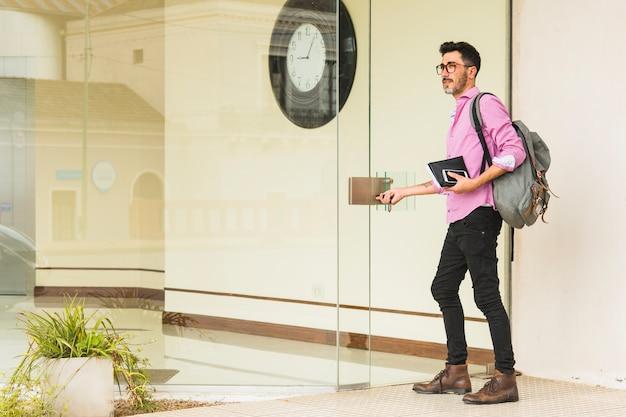 Uomo moderno con il suo zaino tenendo il diario e il telefono cellulare in piedi all'ingresso della porta di vetro Foto Gratuite