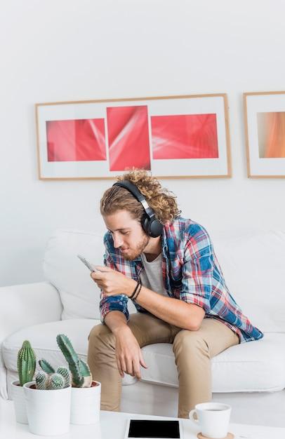 Uomo moderno con smartphone sul divano Foto Gratuite