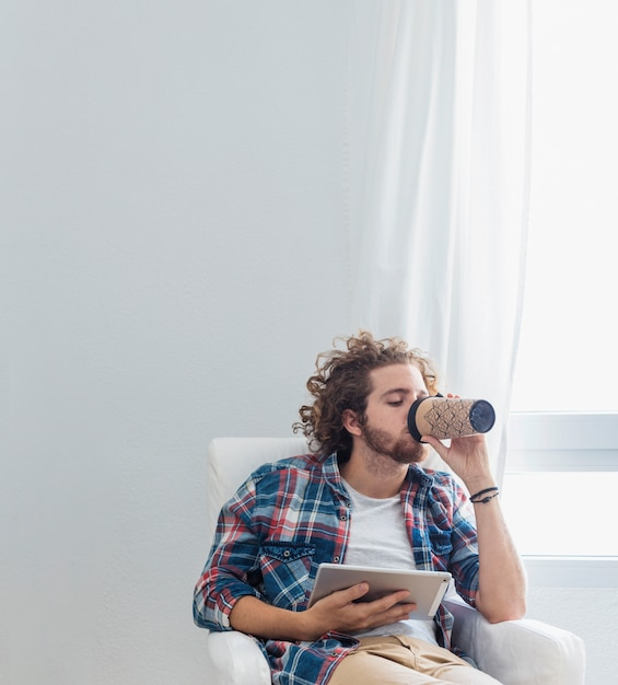 Uomo moderno con tavolo sul divano Foto Gratuite