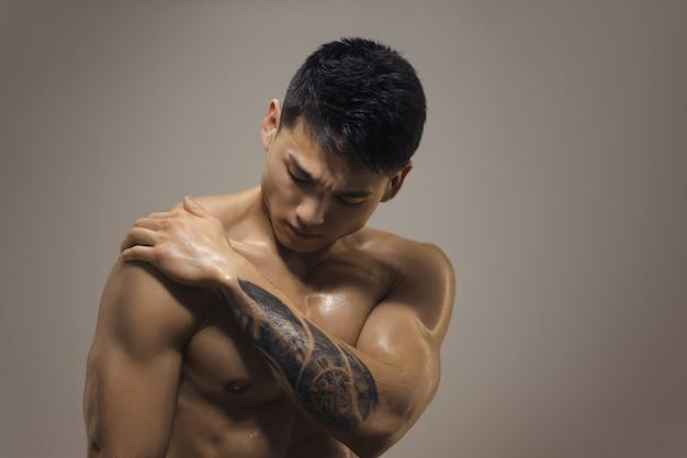 Uomo muscolare atletico che ha dolori articolari della spalla. Foto Premium