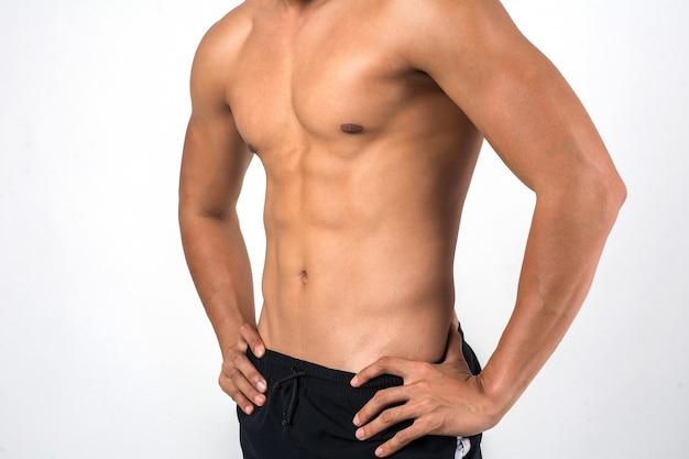 Uomo muscolare che mostra sei addominali del pacchetto isolati su fondo bianco. Foto Gratuite