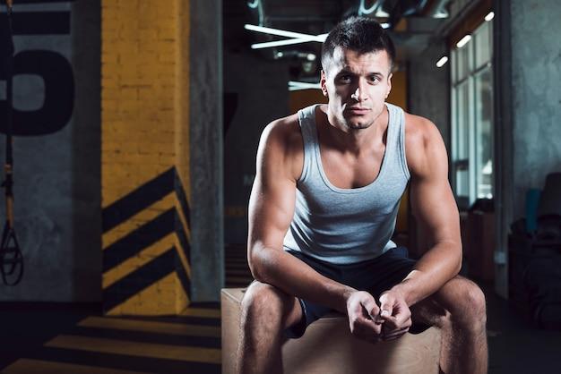 Uomo muscolare che si siede sulla scatola di legno nel fitness club Foto Gratuite