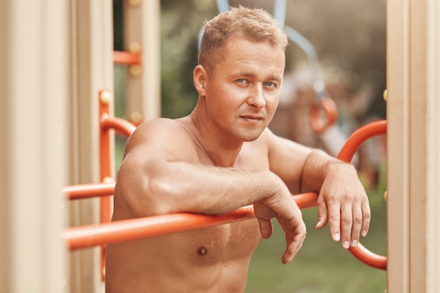 Uomo muscoloso a torso nudo dall'aspetto accattivante, posa all'aperto sul campo sportivo, ama l'allenamento di strada Foto Gratuite