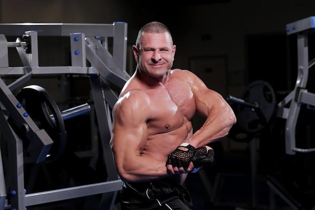 Uomo muscoloso bello in una palestra Foto Gratuite