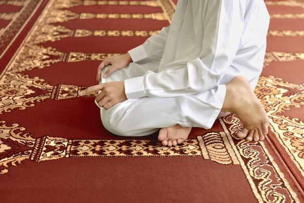 Uomo musulmano che si inginocchia mentre si prega di dio Foto Premium