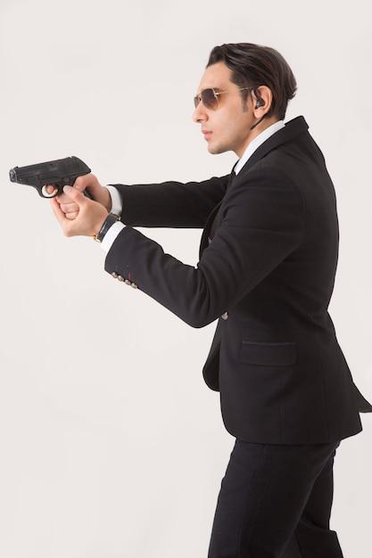 Uomo nella serie di affari e pistola su fondo bianco Foto Gratuite