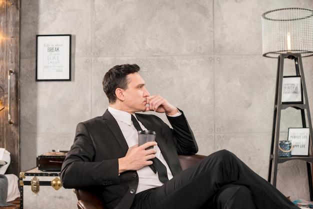 Uomo pensieroso che tiene tazza di caffè nella sala Foto Gratuite