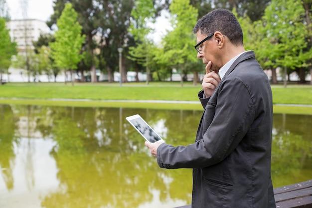 Uomo pensieroso che utilizza compressa e in piedi nel parco della città Foto Gratuite