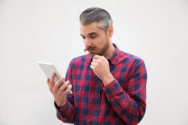 Uomo pensieroso con la mano sul mento utilizzando tablet pc Foto Gratuite