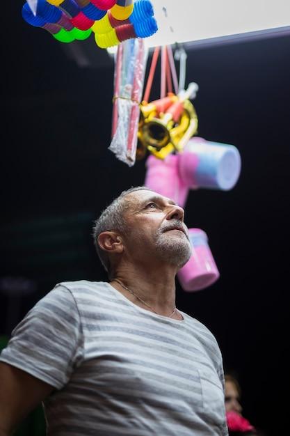 Uomo più anziano che esamina il chiosco del giocattolo Foto Gratuite