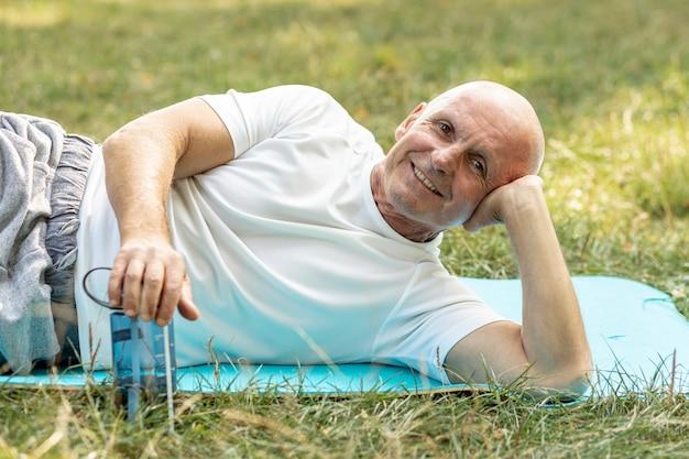 Uomo più anziano felice che riposa sulla stuoia di yoga su erba Foto Gratuite