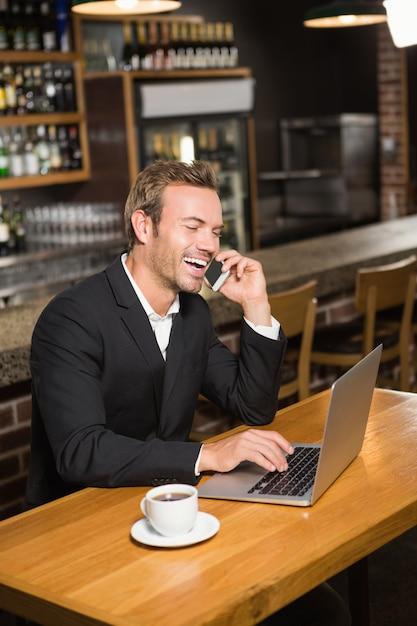 Uomo premuroso che per mezzo del computer portatile e dello smartphone Foto Premium