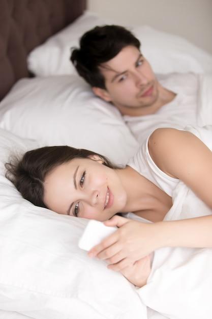 Uomo preoccupato che sospetta la sua fidanzata che tradisce usando il cellulare i Foto Gratuite