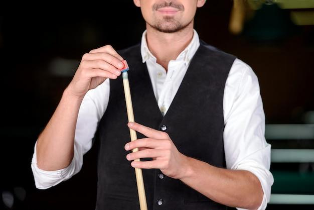 Uomo professionale che gioca a biliardo nel club di biliardo scuro Foto Premium
