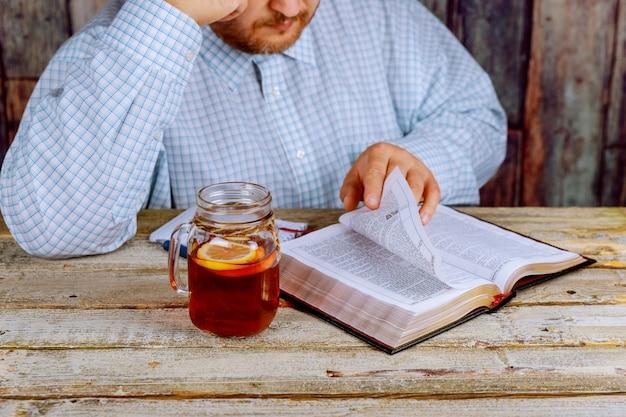 Uomo seduto a un tavolo a leggere la bibbia Foto Premium