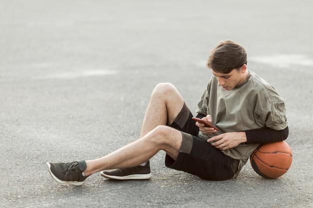 Uomo seduto con un pallone da basket Foto Gratuite