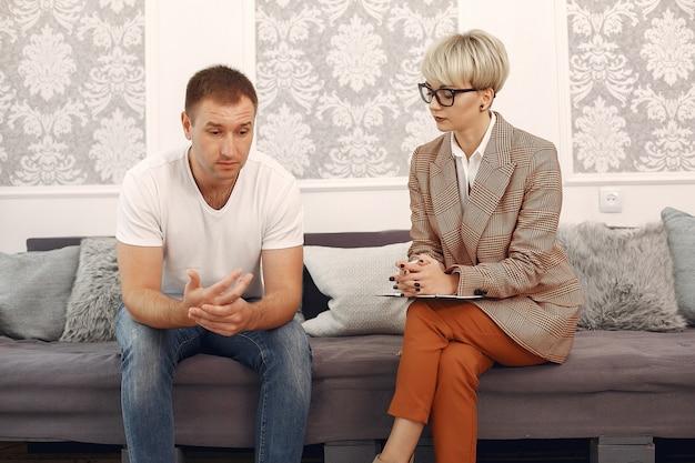 Uomo seduto nell'ufficio dello psicologo e parlando di problemi Foto Gratuite