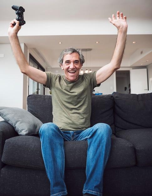 Uomo senior allegro che si siede sul sofà che la alza armi che tengono la leva di comando a casa Foto Gratuite