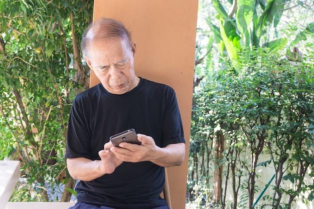 Uomo senior asiatico felice che per mezzo del telefono cellulare a casa Foto Premium