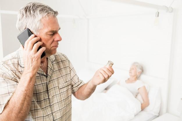 Uomo senior che chiama a causa delle pillole a casa Foto Premium