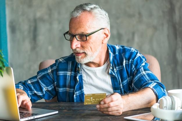 Uomo senior che fa spesa online tramite il computer portatile Foto Gratuite