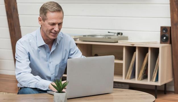 Uomo senior che guarda attraverso internet Foto Gratuite
