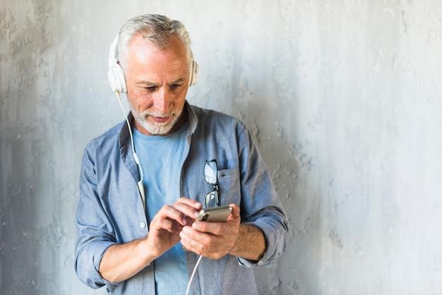 Uomo senior che sta davanti alla musica d'ascolto del muro di cemento sulla cuffia Foto Gratuite