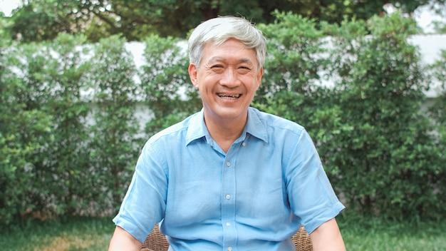 Uomo senior cinese asiatico del ritratto che ritiene sorridere felice a casa. il maschio più anziano si rilassa il sorriso a trentadue denti che guarda mentre si trova nel concetto del giardino a casa di mattina. Foto Gratuite