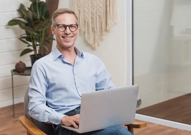 Uomo senior con i vetri che tengono un computer portatile Foto Gratuite