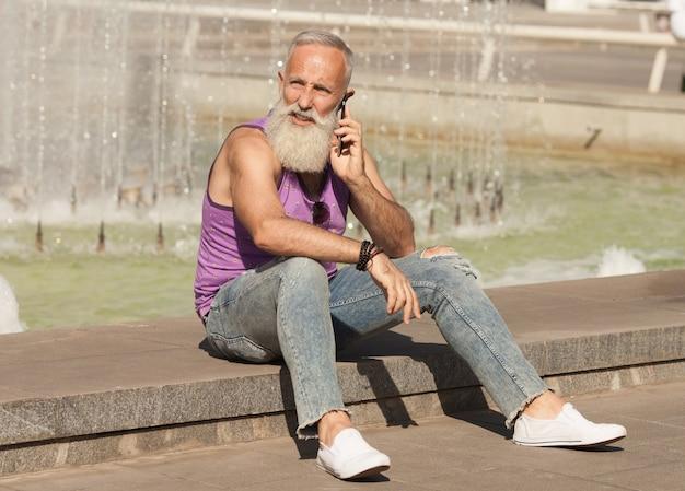 Uomo senior d'avanguardia che utilizza smartphone nel centro del centro all'aperto - maschio maturo di modo divertendosi con la nuova tecnologia di tendenze - tecnologia e concetto anziano allegro di stile di vita Foto Premium