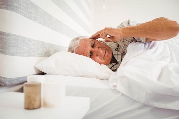 Uomo senior frustrato che si trova sul letto in camera da letto Foto Premium