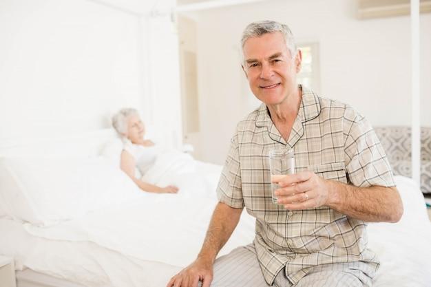 Uomo senior pacifico che tiene bicchiere d'acqua a casa Foto Premium