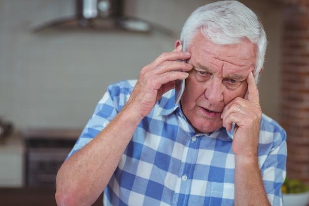 Uomo senior preoccupato che parla sul telefono cellulare Foto Premium