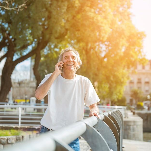 Uomo senior sorridente che sta nel parco che parla sul telefono cellulare Foto Gratuite