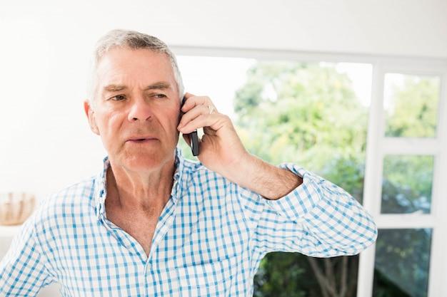 Uomo senior su una telefonata nella cucina Foto Premium