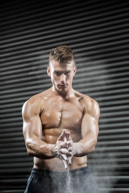 Uomo senza camicia che applaude le mani con talco alla palestra di crossfit Foto Premium