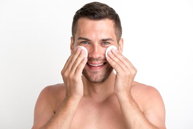 Uomo senza camicia che pulisce il suo fronte con i cuscinetti di cotone dell'ovatta sopra fondo bianco e che esamina macchina fotografica Foto Gratuite