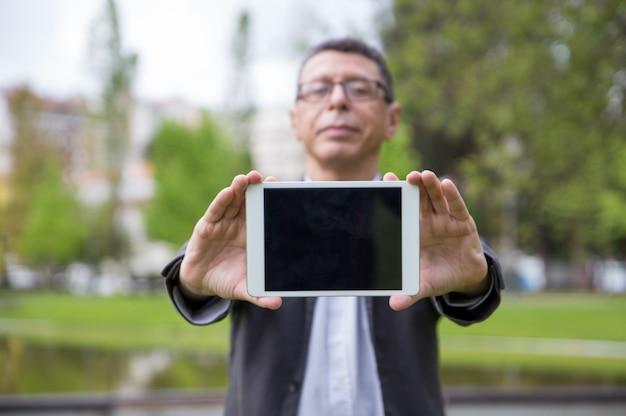 Uomo serio che mostra lo schermo della compressa allo spettatore in parco Foto Gratuite