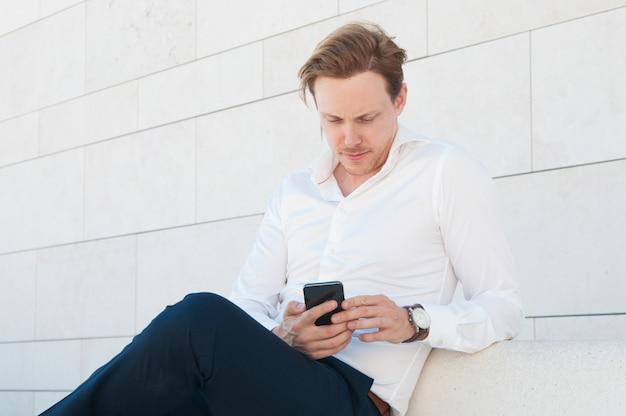 Uomo serio di affari che per mezzo dello smartphone sul banco all'aperto Foto Gratuite