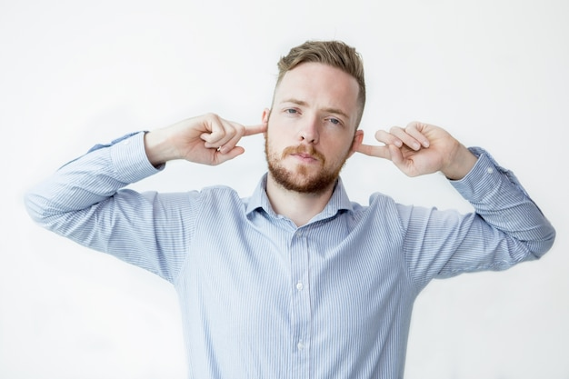 Uomo serio fermare le orecchie con le dita Foto Gratuite