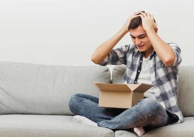 Uomo sorpreso della scatola di consegna Foto Gratuite