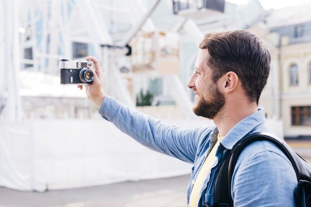 Uomo sorridente barbuto che prende selfie con la retro macchina fotografica durante il viaggio Foto Gratuite