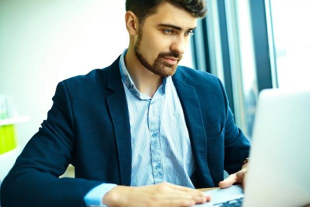 Uomo sorridente bello bello dei pantaloni a vita bassa di giovane modo nel caffè della città durante l'ora di pranzo con il taccuino in vestito Foto Gratuite