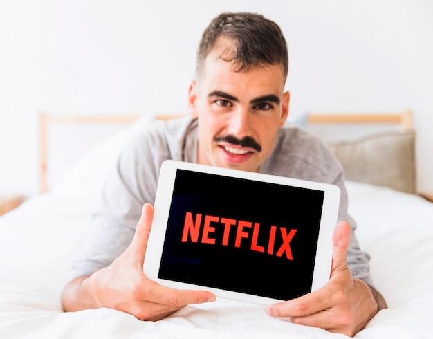 Uomo sorridente che dimostra il logo netflix in camera da letto Foto Gratuite