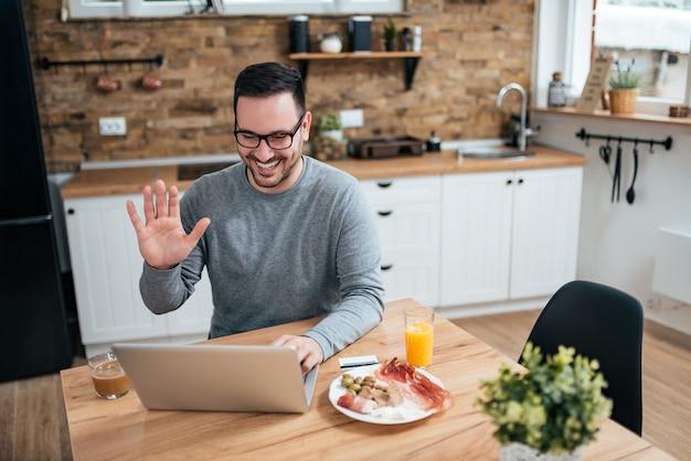 Uomo sorridente che gode della prima colazione nella cucina e che ha una videochiamata sul computer portatile. Foto Premium