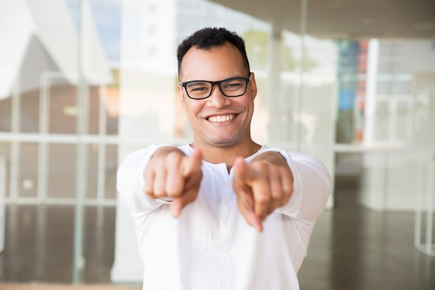 Uomo sorridente che guarda l'obbiettivo, che punta verso la telecamera con le mani Foto Gratuite
