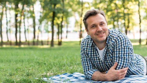 Uomo sorridente che guarda l'obbiettivo che si trova sulla coperta nel parco Foto Gratuite