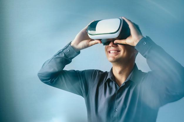 Uomo sorridente che indossa una cuffia avricolare di realtà virtuale Foto Premium
